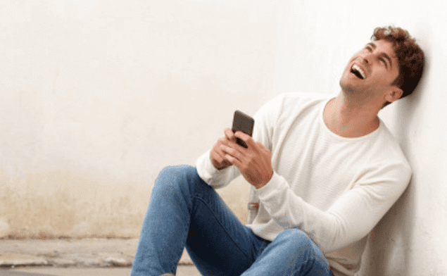 men laughing at phone conversation